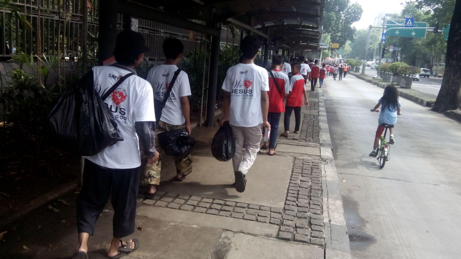 Para relawan membawa kantong-kantong plastik yang penuh dengan sampah.
