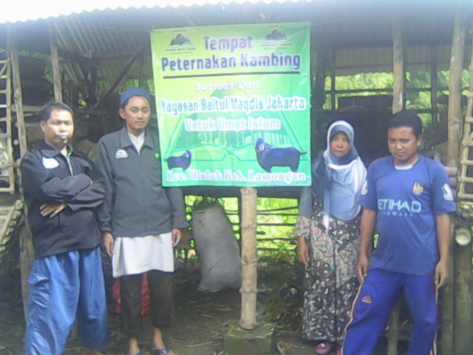 Foto para da'i dengan salah satu masyarakat di depan kandang kambing bantuan YBM.