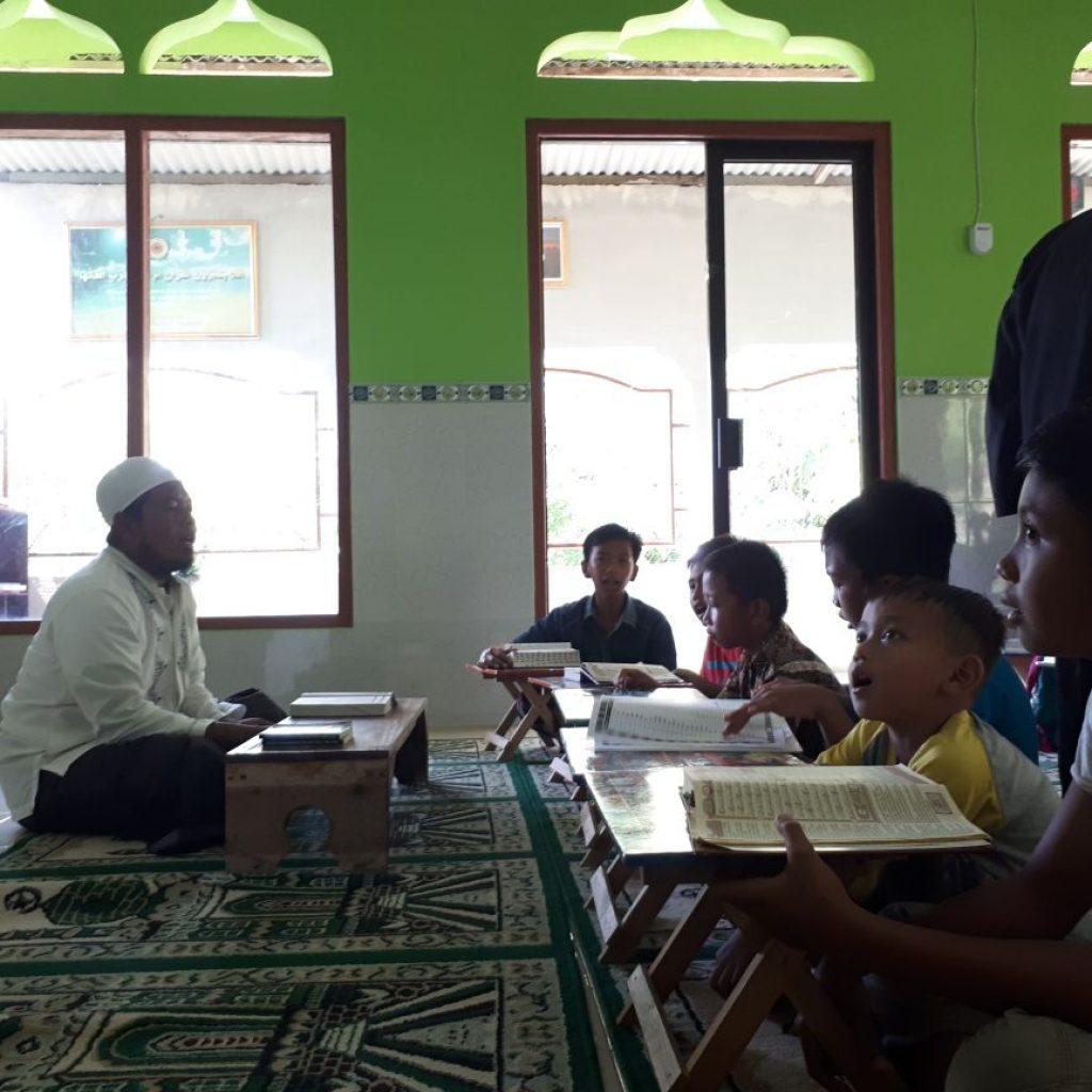 ust. farosyid yang sedang mangejarkan Al Quran kepada anak anak muallaf