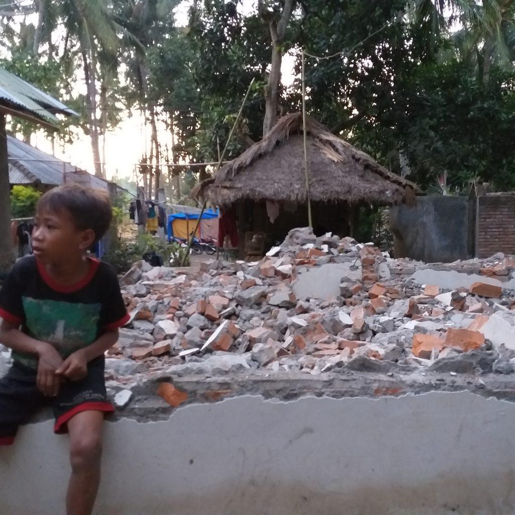seorang Anak dengan Reruntuan Rumahnya